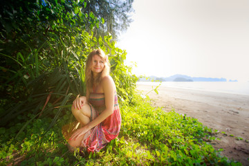 blonde girl in long dress  on grass near beach