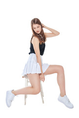 Young fashion girl in white skirt sitting on the chair isolated