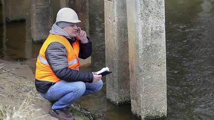Engineer talking on cell phone under the bridge