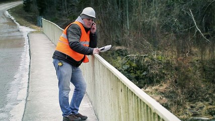 Engineer  talking on cell phone on the bridge
