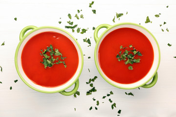 Classic tomato soup with parsley on white wooden background