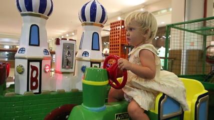 little blonde child is happy sitting in toy railway