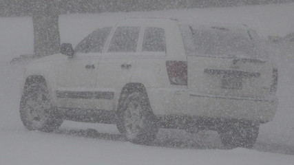 Snowing Hard on a White Jeep Car