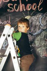 little cute boy at blackboard in classroom, back to school