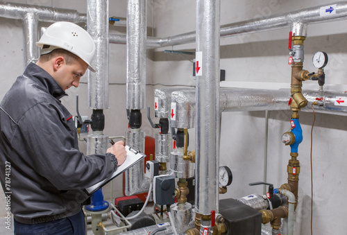 Technician inspecting heating system in boiler room - 78741327