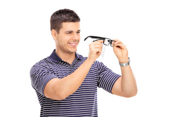Young man wiping his glasses