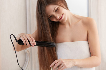 Woman straightening hair with straightener