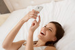 Portrait of a happy woman lying on bed  using a smart phone
