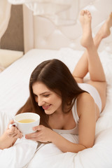 Woman Holds Cup of Tea Lying on the Bed.