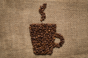 Coffee mug made from roasted beans on burlap background