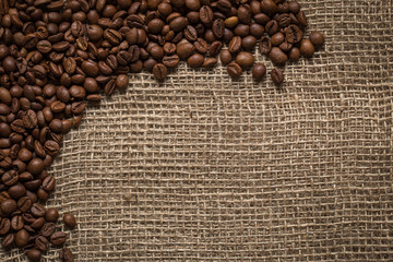 Scattered Coffee Beans on burlap background