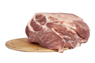 Raw pork meat on a round board isolated on white