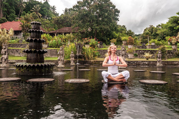 Women meditation near Water Palace Tirthagangga. Bali Indonesia