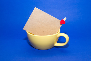 Envelope with heart  in the yellow cup on a blue background.