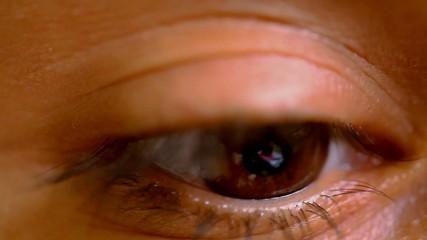 Female brown eye opens and wonders frightened. Macro video