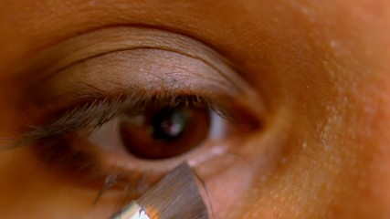 Female brown eye doing make-up. Macro video time lapse speed up