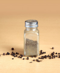Glass jar with black pepper peas on a brown wooden surface