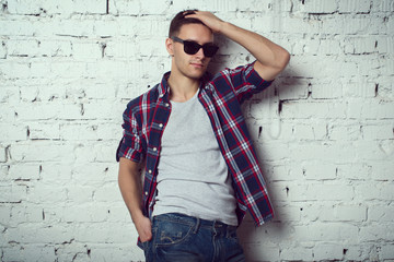 Casual handsome attractive hipster guy man with sunglasses his