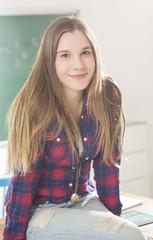 Junges Mädchen sitzt auf Tisch im Klassenzimmer