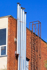 Metal smoke stacks and ladder on the wall of a building