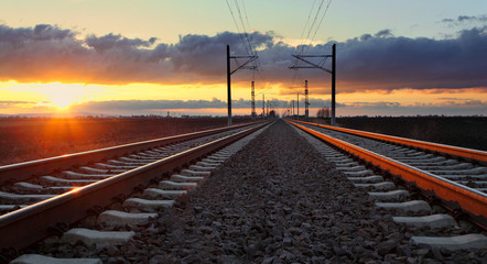 Railroad at sunset with sun and lines
