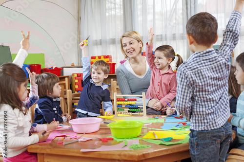 Fototapeta Teacher with children in kindergarten
