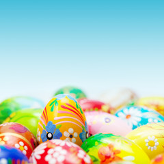 Handmade Easter eggs on blue sky. Spring patterns art, unique.