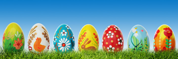 Hand painted Easter eggs on grass. Panorama, banner.