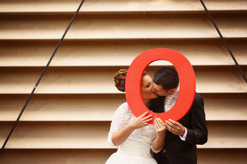 Bride and groom holding bid red O letter