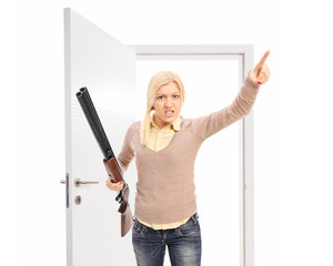 Angry woman with rifle threatening someone