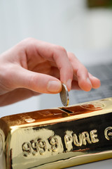 hand droping a coin in gold ingot shaped piggy bank money box