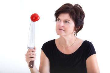 Woman with knife looks at skewered tomato