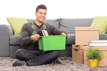 Man sitting by a sofa with moving boxes around him