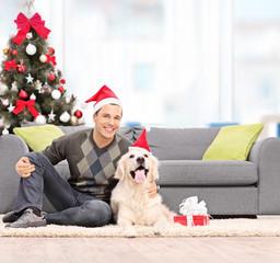 Man and a dog with Santa hats sitting at home
