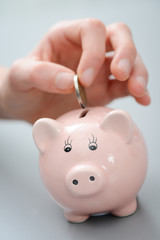 close up detail of hand droping coin in piggy bank money box