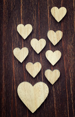 One big and lots of small wooden hearts placed nicely on a vinta