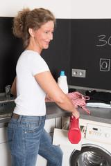 Frau fült Waschmittel in die Waschmaschine