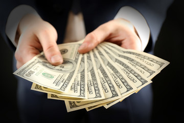 Businessman giving money on dark background
