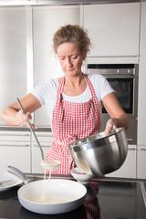 Frau kocht Pfannkuchen