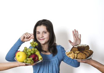 Girl choose to eat organic fruits - grapes, apples, pears