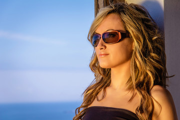 Curly blonde girl with black top and sunglasses