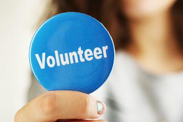 Round volunteer button in hand close-up