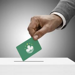 Black male holding flag. Voting concept - Macau