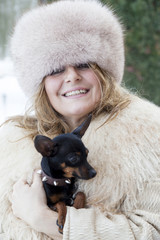 pretty lady cuddle her little dog in winter time