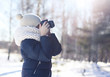 Child photographer takes picture on the digital camera outdoors