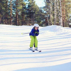 Professional skier boy skiing in the forest, sunny winter day