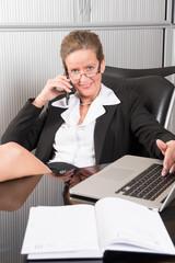 Chefin im Büro am Telefon