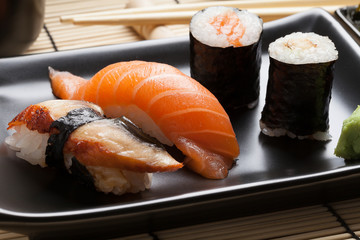 Japanese sushi: nigiri and maki on black plate.