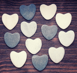 Twelve stone hearts placed nicely on a vintage wood background