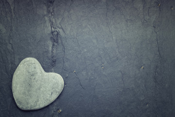 Gray zen heart shaped rock in the corner on a tile background